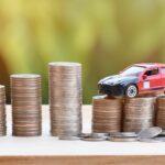 speelgoed auto op een stapel munten als beeldvorming voor een lease auto van lease'm