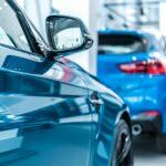 twee blauwe auto's in een showroom voor het online aanbod