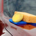 Sponzen en een doek op een auto voor autoreiniging op locatie